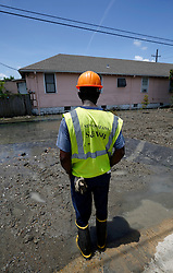23 July 2013. New Orleans, Louisiana.<br /> Following a major break in an old 30-inch water main, officials and workers from New orleans Sewerage and Water board struggle to contain the millions of gallons of water flooding homes and streets in The Carrolton neighbourhood. Huge investment in public infrastructure is required to repair and upgrade the ageing water delivery system in the city. Following the break, low water pressure and a public boil advisory affected tens of thousands of Uptown residents.<br /> Photo; Charlie Varley