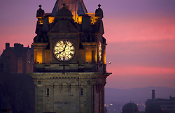 Sunset from Edinburgh's Calton Hill. The clock of the Balmoral Hotel is in the foreground with Edinburgh Castle lit up in purple complimenting the warm colours of the sunset.