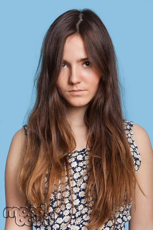 Portrait of serious young woman over blue background