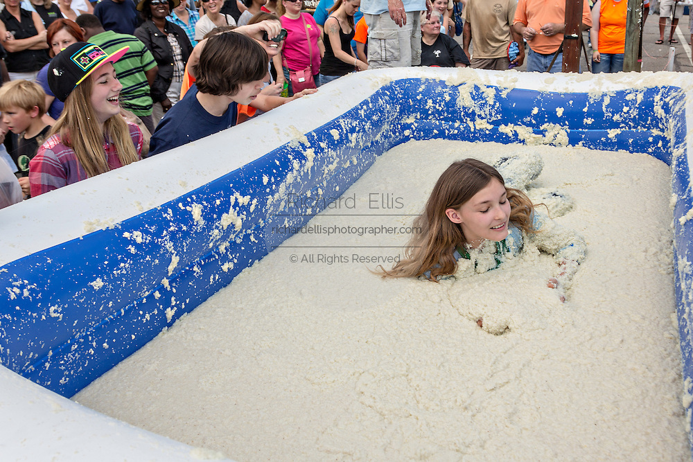 A girl rolls in a vat of grits during the World Grits Festival rolling in the grits contest April 12, 2014 in St. George, South Carolina. Contestants have to roll in a vat of grits and the one with the most grits sticking to their body wins. Grits are a tradition Southern dish of thick maize-based porridge made from dried corn hominy.
