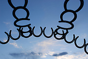 An arched sculpture of horseshoes is silhouetted against a blue sky and setting sun at the Bar-M Chuckwagon in Moab, Utah on June 15, 2006.