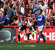James Tarkowski celebrating scoring with Ramallo Jota in front of their ex captain Jonathan Douglas during the Sky Bet Championship match between Brentford and Ipswich Town at Griffin Park, London, England on 8 August 2015. Photo by Matthew Redman.