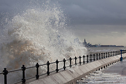 © Licensed to London News Pictures. 03/01/2014.New Brighton, UK . Waves hit New Brighton promenade as the high tide arrives, with the Liverpool skyline in the background. Photo credit : Andrew Dawson/LNP
