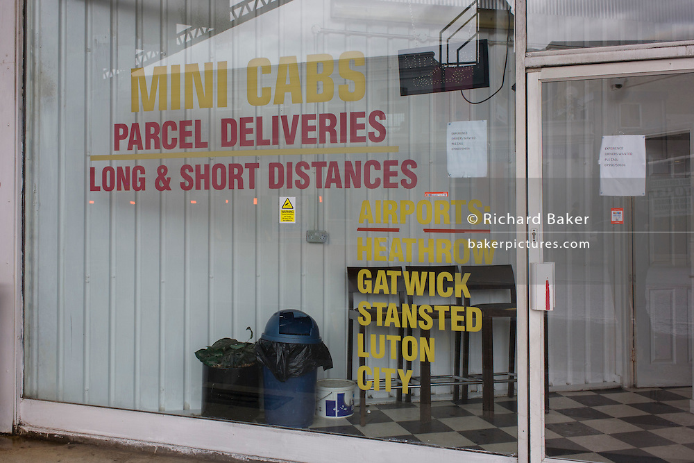 Local minicab office window in Borough, south London.
