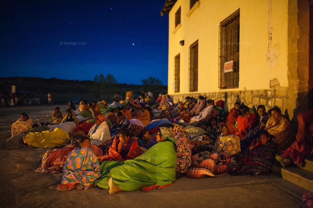 Un grupo de mujeres con sus hijos duermen al aire libre junto a un albergue, mientras los pintos danzan durante toda la noche del Jueves Santo en Norogachi, México, el 9 de abril de 2009.
