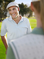Young golfers on course focus on smiling man