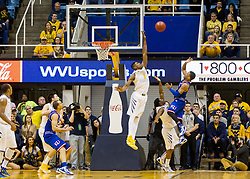 Kansas Jayhawks guard Frank Mason III (0) shoots a shot in the final minute over West Virginia Mountaineers forward Jonathan Holton (1) during the second half at the WVU Coliseum.
