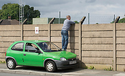 LIVERPOOL, ENGLAND - Wednesday, August 18, 2010: A Liverpool supporter uses his car to get a good vantage point to peer over the wall of the club's Melwood training ground to get a glimpse of the players training ahead of the UEFA Europa League Play-Off 1st Leg match against Trabzonspor A.S. (Pic by: David Rawcliffe/Propaganda)
