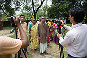 An extended family arrive at a government compound in the town of Debiganj to sign documents and filmed by local TV journalists. Originally they asked if they could go to India after the disbanding of the enclaves but later changed their mind and decided to stay. Their request was allowed and formalised on this day.<br /> <br /> On July 31st 2015 the enclaves that formed one of the world's most complicated borders were officially absorbed in to the countries that surrounded them in a land-mark land swap between India and Bangladesh. The people that lived in them will finally receive citizenship.<br /> <br /> Enclaves are small pockets of sovereign land completely surrounded by another sovereign nation. Approximately 160 enclaves, known as chitmahals, exist on either side of the India-Bangladesh border. For 68 years the 50,000 plus inhabitants of these enclaves have lived a difficult existence, stranded from their home nation and ignored by the country that surrounds them. <br /> <br /> In theory even leaving their enclaves is illegally crossing an international border and for decades it has been very difficult for them to receive even the most basic of rights whether education or health. Even the police have no jurisdiction in the enclaves leaving them essentially lawless.