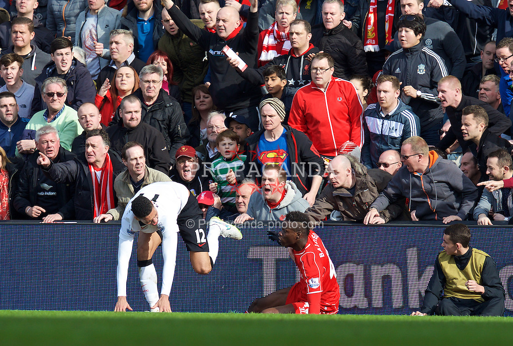 LIVERPOOL, ENGLAND - Sunday, March 22, 2015: Liverpool's Mario Balotelli reacts after being pushed into the advertising hoardings by Manchester United's Chris Smalling during the Premier League match at Anfield. (Pic by David Rawcliffe/Propaganda)