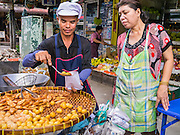 "04 OCTOBER 2012 - BANGKOK, THAILAND: A vendor who sells fried snacks like dough balls and banana fritters, works on Sukhmvit Soi 22 in central Bangkok.  Thailand in general, and Bangkok in particular, has a vibrant tradition of street food and ""eating on the run."" In recent years, Bangkok's street food has become something of an international landmark and is being written about in glossy travel magazines and in the pages of the New York Times.       PHOTO BY JACK KURTZ"