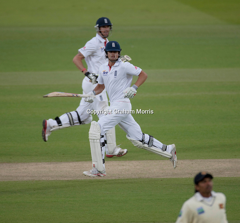 Alastair Cook runs past Kevin Pietersen (behind) under floodlights during the second npower Test Match between England and Sri Lanka at Lord's.  Photo: Graham Morris (Tel: +44(0)20 8969 4192 Email: sales@cricketpix.com) 06/06/11