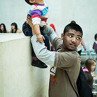 A young Middle Eastern father playing with his son at the British Museum in London.