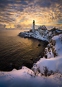 A blanket of white covers the ground in front of Portland Head Lighthouse in Cape Elizabeth, Maine