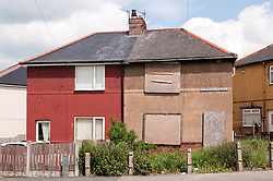 Derelict house next to one that is occupied, Thurnscoe, South Yorkshire. The council estate is being regenerated