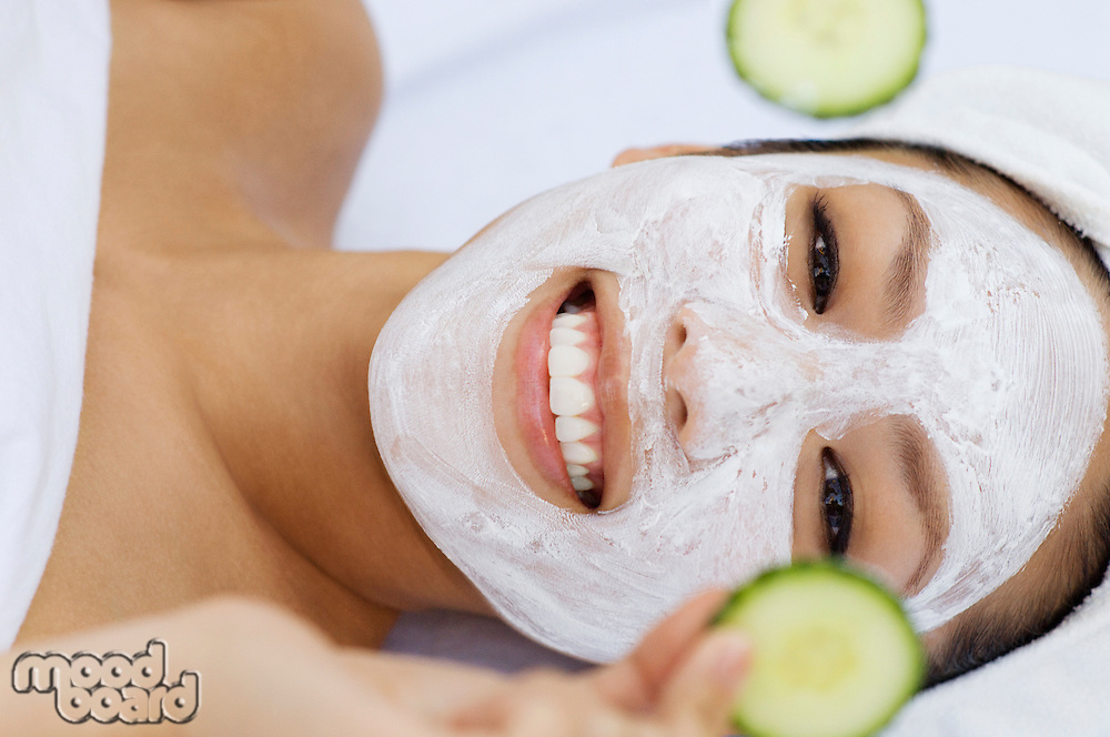 Young woman having facial treatment, holding cucumbers, portrait