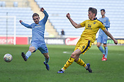 Oxford United defender Rob Dickie (4) clears the ball under pressure from Coventry City midfielder (on loan from Derby County Luke Thomas (23) during the EFL Sky Bet League 1 match between Coventry City and Oxford United at the Ricoh Arena, Coventry, England on 23 March 2019.