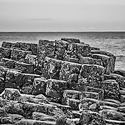 The Giant's Causeway rises out of the water like the start of a paved path from the north of Ireland headed to Scotland.  The stones are natural basalt.