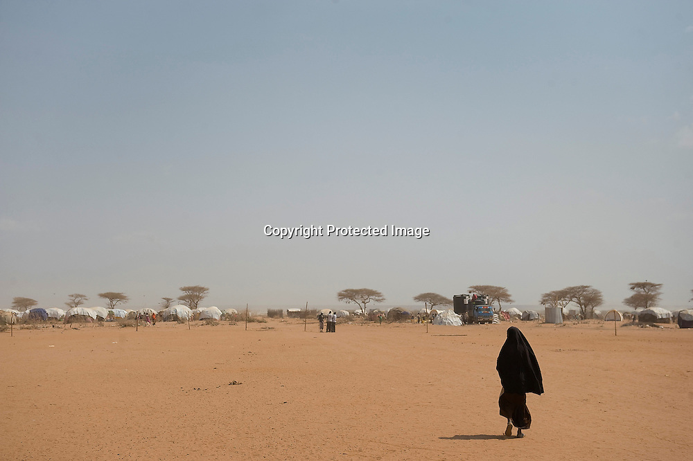 A woman walks near refugee dwellings in the Dadaab refugee camps in northeastern Kenya.