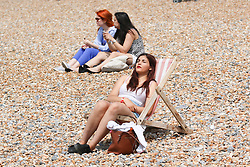 © Licensed to London News Pictures. 12/07/2014. Brighton, UK. A woman sunbathing on Brighton beach. With temperatures around the 23C down the South Coast thousands of people taking a weekend away down on the beach. Photo credit : Hugo Michiels/LNP