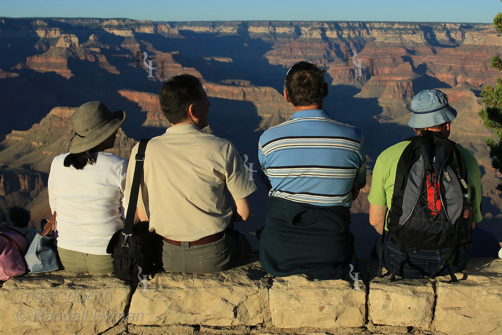 Four tourists sit on stone wall overlook at Hopi Point on the South Rim of Grand Canyon National Park, Arizona.