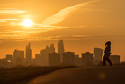Primrose Hill, London, October 28th 2016. A woman runs up Primrose Hill as the sun rises over London's skyscrapers.