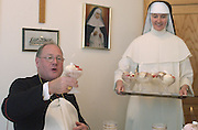 Archbishop Timothy Dolan enjoys a flaming Polish dessert in Milwaukee in 2002. (Sam Lucero photo)