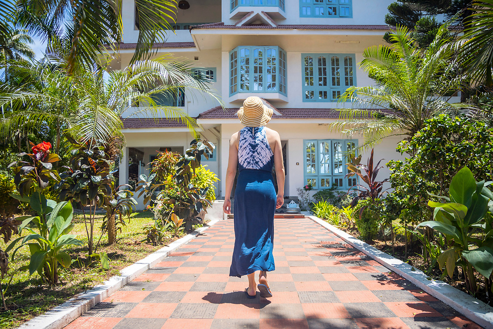 VARKALA, INDIA - 27th September 2019 - Tourist wearing summer dress walks up to colonial building hotel amid tropical flora and greenery on a sunny day at Varkala Cliff Beach, Kerala, Southern India