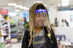 © Licensed to London News Pictures. 15/04/2020. London, UK. Waitrose employee Abigail (21) wears a face shield while on the shop floor. Staff at Waitrose at Westfield White City are now issued with PPE (personal protection equipment) before starting shift which they are encouraged but not obliged to wear when coming into contact with high volumes of shoppers. The face shields protect the wearer from aerosol ejection, one of the key vectors associated with the transmission of the coronavirus COVID-19. While frontline workers in other sectors notably in healthcare - NHS and care homes - are struggling to access appropriate protection some supermarkets have taken matters into their own hands providing their own PPE and cleaning protocols. Photo credit: Guilhem Baker/LNP