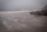 The tide comes in along a rainy Oregon coast.