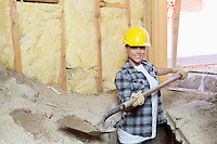 Portrait of a happy female contractor digging sand at construction site
