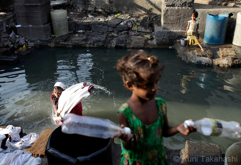 A woman washes clothes in reservoir in Dharavi, India's largest slum, in Mumbai on Oct 26, 2009. The running water is available only 3 hours in the morning and 3 hours in the evening in the community. Due to luck of rainfall in this year's monsoon season, the authorities in Mumbai imposed at least 25 per cent water cut as it faces one of the worst water shortages in its history. Photo by Kuni Takahashi