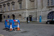 A blue-themed street landscape of a safety fencing, a blue police box and a rider on a blue Boris bike outside Mansion House in the City of London.