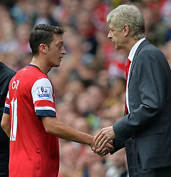 Arsenal's Mesut Ozil shakes hands with Arsenal Manager, Arsene Wenger after being substituted - Photo mandatory by-line: Mitchell Gunn/JMP - Tel: Mobile: 07966 386802 22/09/2013 - SPORT - FOOTBALL - Emirates Stadium - London - Arsenal V Stoke City - Barclays Premier League