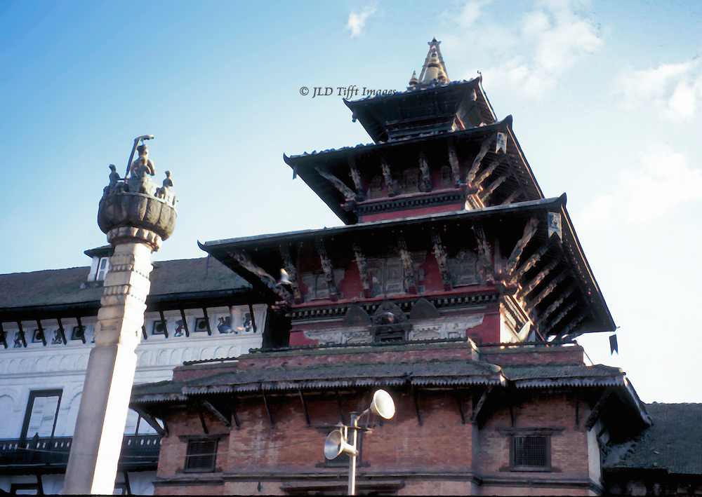 Tiered roofs of the Patan temple Jagannarayan Mandir, with a figure of King Yoganarandra Malla on the top of a column in front of it.  Patan Durbar Square, a UNESCO Monument Zone in the Kathmandu Valley. Temple dated late 16th century.  The king ruled ca. 1685-1706.