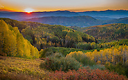 The sun sets over a view of colorful aspen trees. The view is from Rainbow Ridge on Buffalo Pass near Steamboat Springs, Colorado.