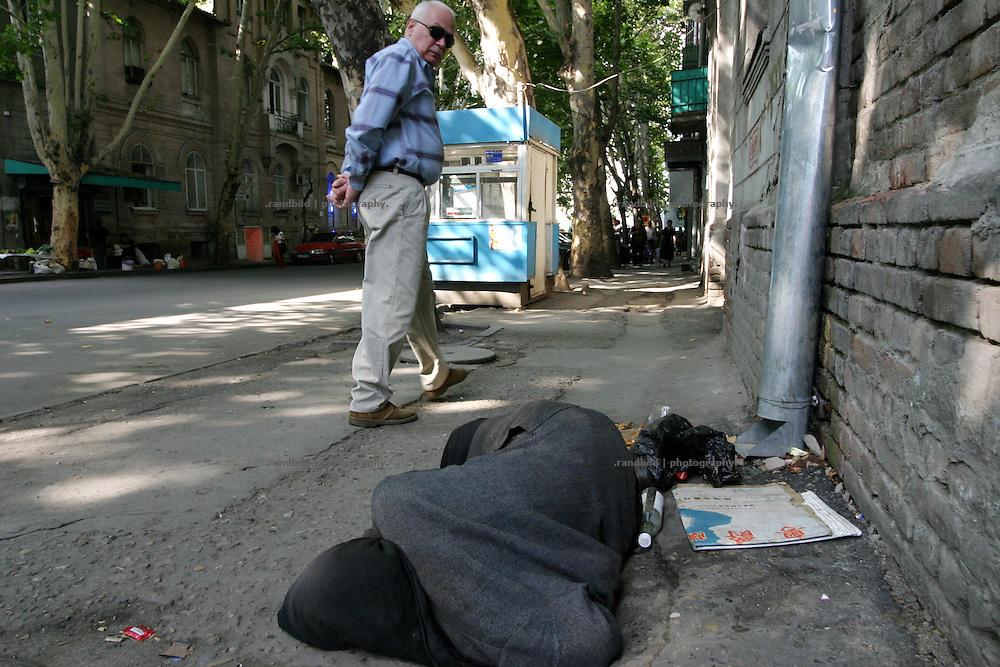 In der georgischen Hauptstadt Tilfis geht ein Mann an einer am Boden liegenden Obdachlosen Frau vorrueber. ..A homeless woman lies on the ground in a street of old Tbilissi, Georgia.