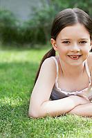 Little Girl Lying in Grass in backyard portrait