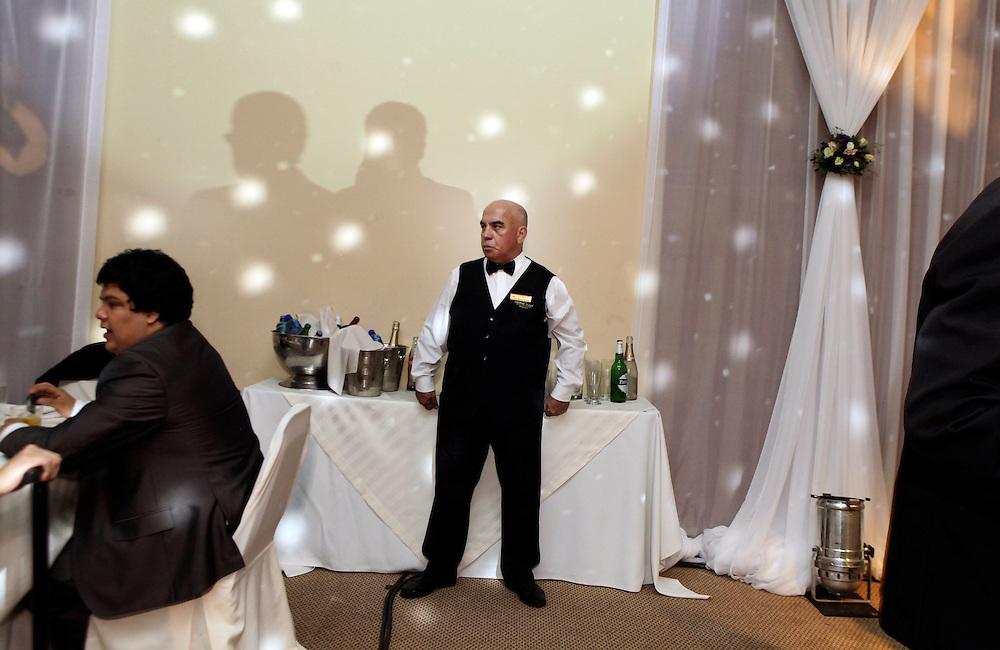 Carpeta 18 Foto 06<br /> Un mozo mira atento a los concurrentes a la fiesta de un casamiento  en Asuncion, Paraguay el 8 de enero de 2012. (Jorge Saenz)<br /> <br /> &quot;Todo era una Fiesta&quot;:<br /> Por mas crisis que ataquen la econom&iacute;a publica y privada, la clase alta de Paraguay tal como la de otros pa&iacute;ses, no limita en lo mas m&iacute;nimo su costumbre de festejar las bodas con una gran inversi&oacute;n econ&oacute;mica en los eventos. Este trabajo presentado es parte de uno mas general en desarrollo sobre la sociedad paraguaya llamado &quot;Las Clases&quot; desde hace mas de 10 a&ntilde;os.