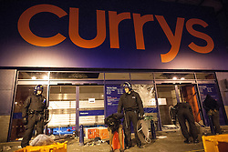 © Licensed to London News Pictures . 08/08/2011 . London , UK . Police detain looters outside a branch of Currys in Brixton during a 2nd night of rioting and looting in London , which followed a protest against the police shooting of Mark Duggan in Tottenham . Photo credit : Joel Goodman/LNP