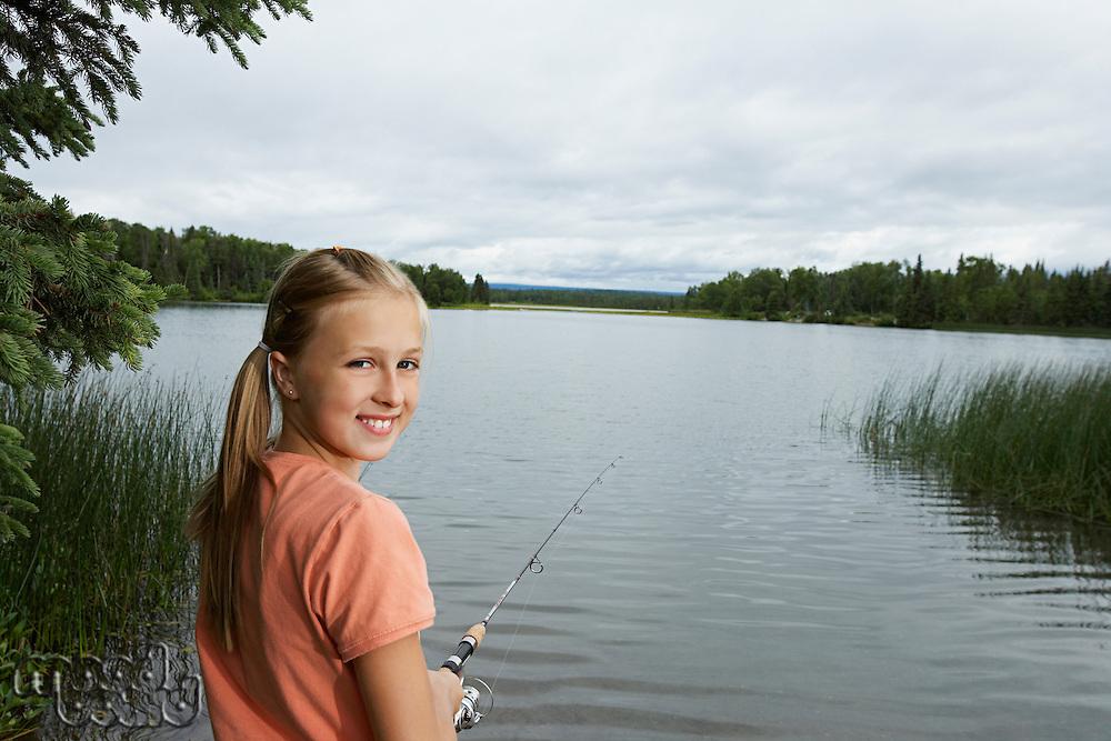 USA, Alaska, teenage girl fishing at lake, portrait