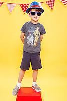 7 year old boy wearing star printed glasses and a red white and blue fedora hat standing on a red pedestal against yellow seamless.<br /> Photographed at the Photoville Photo Booth September 20, 2015