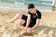Summer Vacation a teen builds a sand castle on the beach Model release available