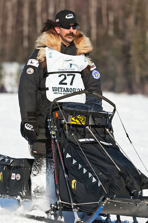 Musher Mike Santos competing in the 39th Iditarod Trail Sled Dog Race on Long Lake after leaving the Willow Lake area at the restart in Southcentral Alaska.  Afternoon.