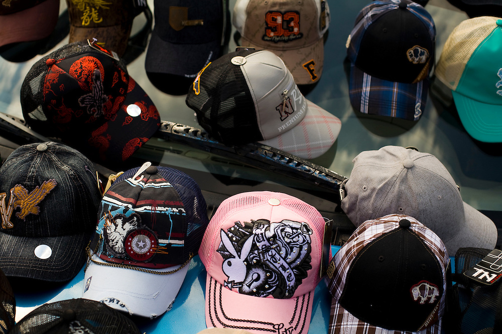 Hats like these are commonly associated with Mexico's Narco Culture.  Youth wear flashy baseball caps and clothing in an attempt to show how wealthy they are, or in an attempt to appear wealthy and powerful.