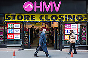 A British city worker walks past an HMV entertainment retail store in the Square Mile, central London, United Kingdom.  The shop is having a closing down sale and due to the economic downturn the British retailing company entered administration in January 2013.