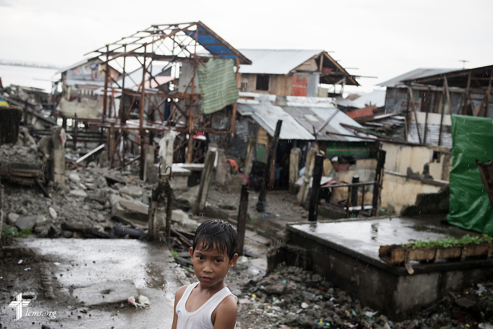 A boy is framed by destruction leftover from Typhoon Haiyan in Tacloban, Leyte Province, Philippines, on Friday, March 14, 2014. LCMS Communications/Erik M. Lunsford