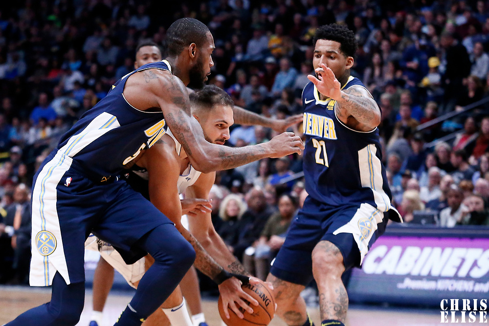 11 November 2017: Orlando Magic forward Evan Fournier (10) drives past Denver Nuggets guard Will Barton (5) ans Denver Nuggets forward Wilson Chandler (21) during the Denver Nuggets 125-107 victory over the Orlando Magic, at the Pepsi Center, Denver, Colorado, USA.