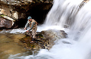 A fly fisherman stands in a trout stream and casts his rod into a pool below a waterfall in North Carolina.