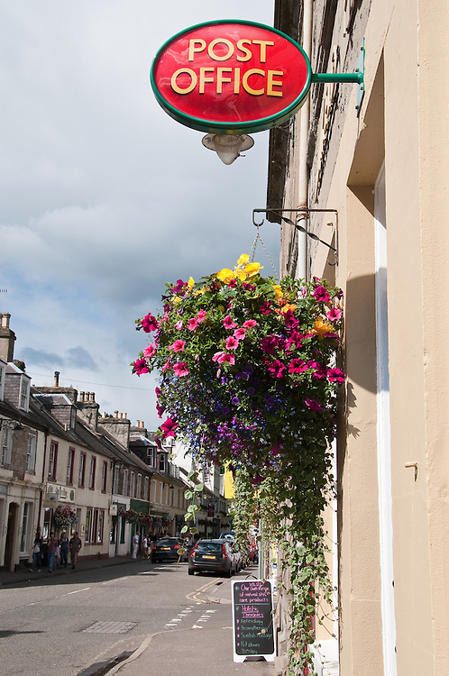 Hanging Basket hangs below Post Office sign in Dunkeld, Scotland